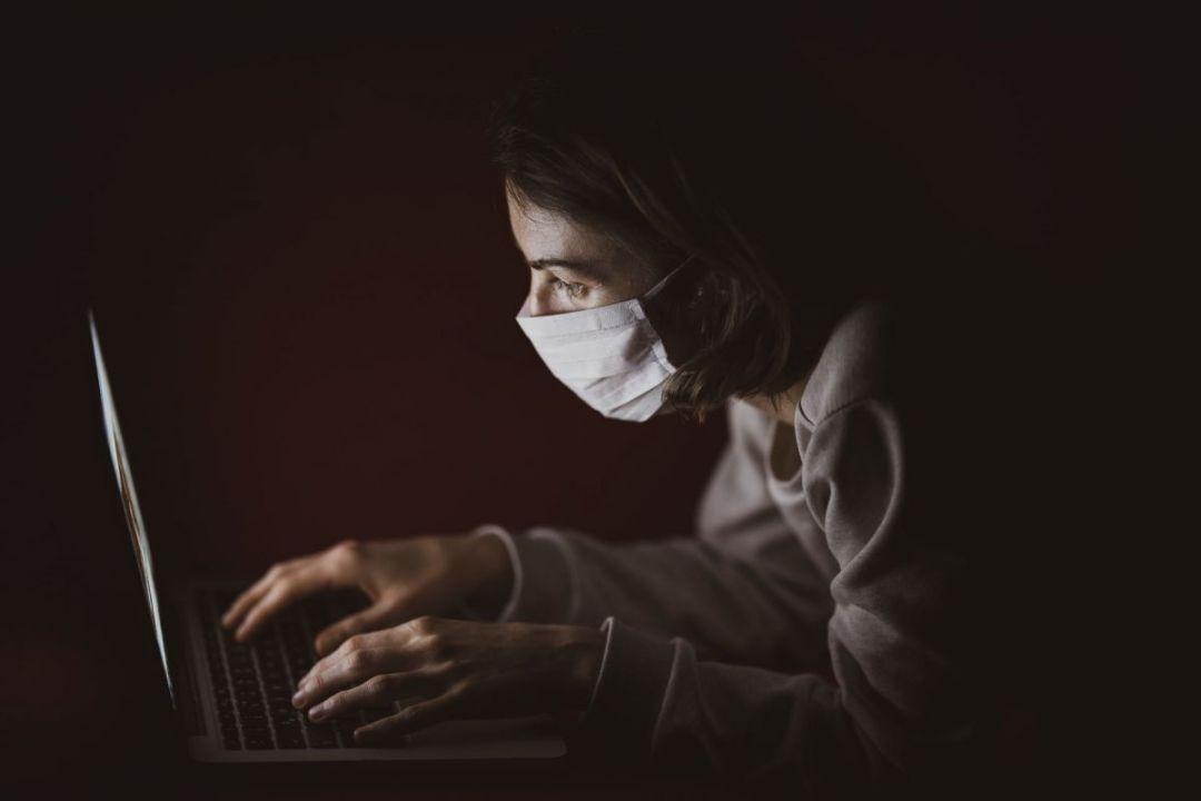 Illustration writer at laptop wearing a mask by engin akyurt on Unsplash